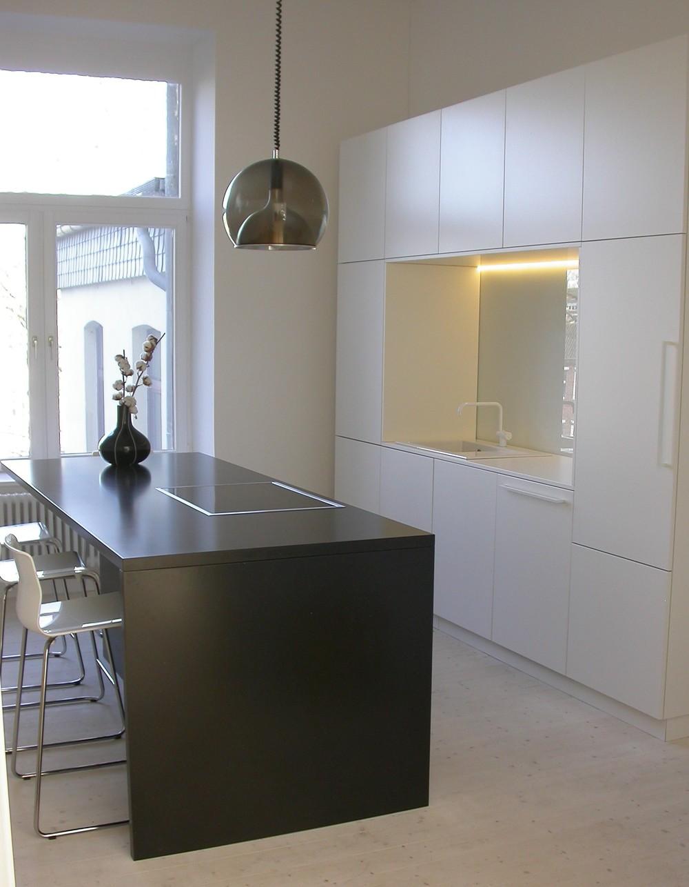 Schwarzer Küchenblock mit integrierter Sitzmöglichkeit, ideal zum schnellem Frühstück oder Kaffee.