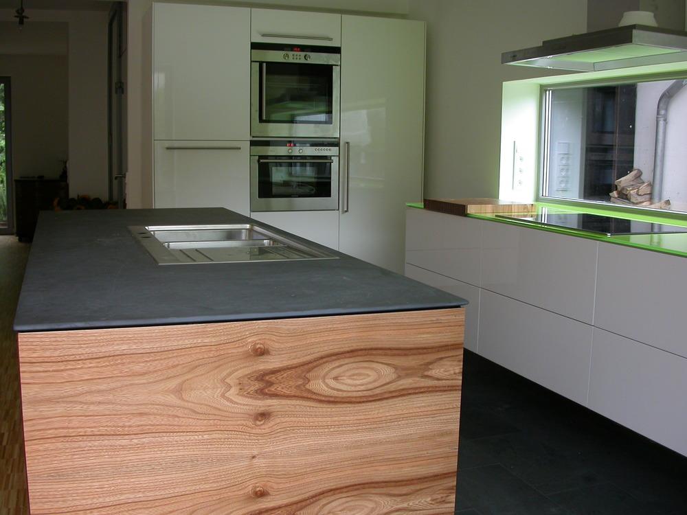 Rüster, Schiefer und Weiß Hochglanz. Geräteschrank im Hintergrund mit hoch eingebautem Kühlschrank und Spülmaschine.