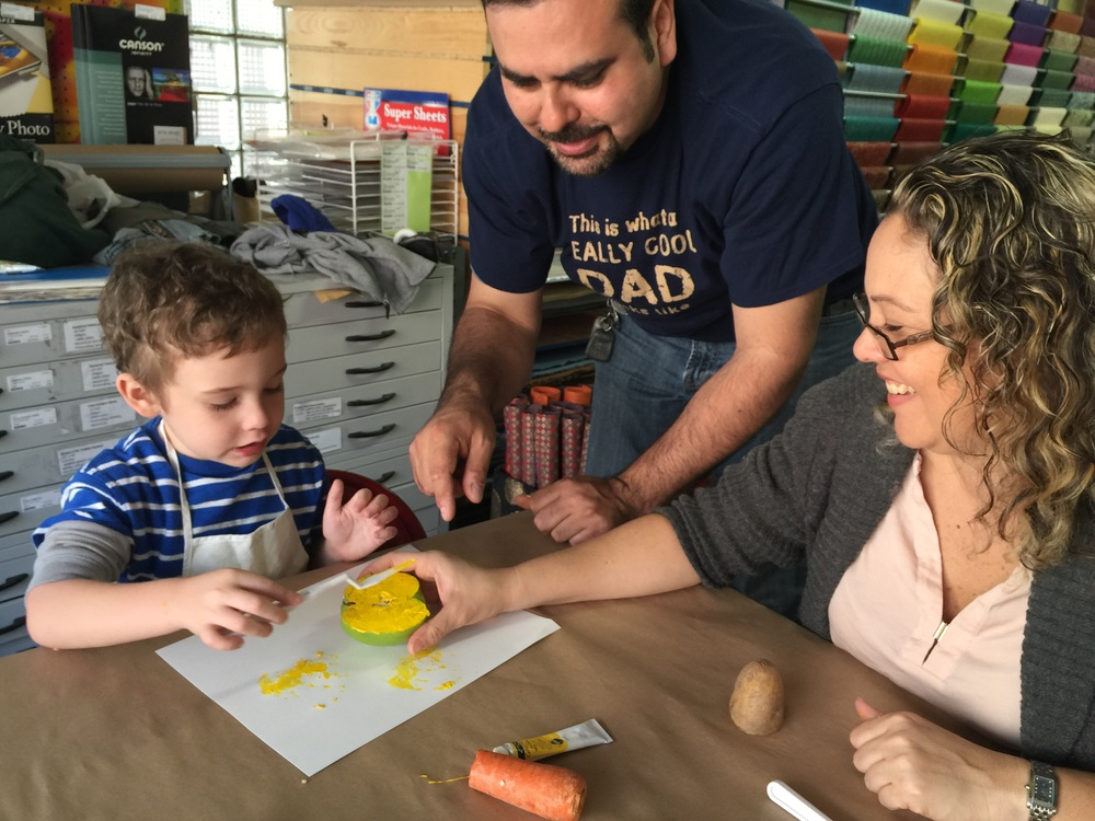 "James & his Mommy & Daddy applying ""primary yellow"" to his Apple for his veggie print! All hands on deck here! We super ❤️ this!!!"