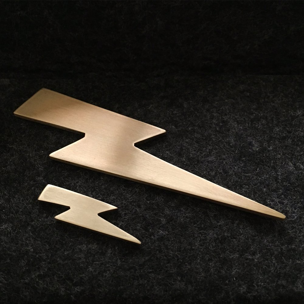 """BOLT""  - hand cut from solid brass  - available as ring, necklace, & earrings  - contact for sizes, price, & availability"