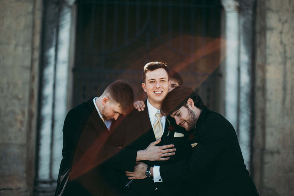 Groom being hugged by three groomsmen.