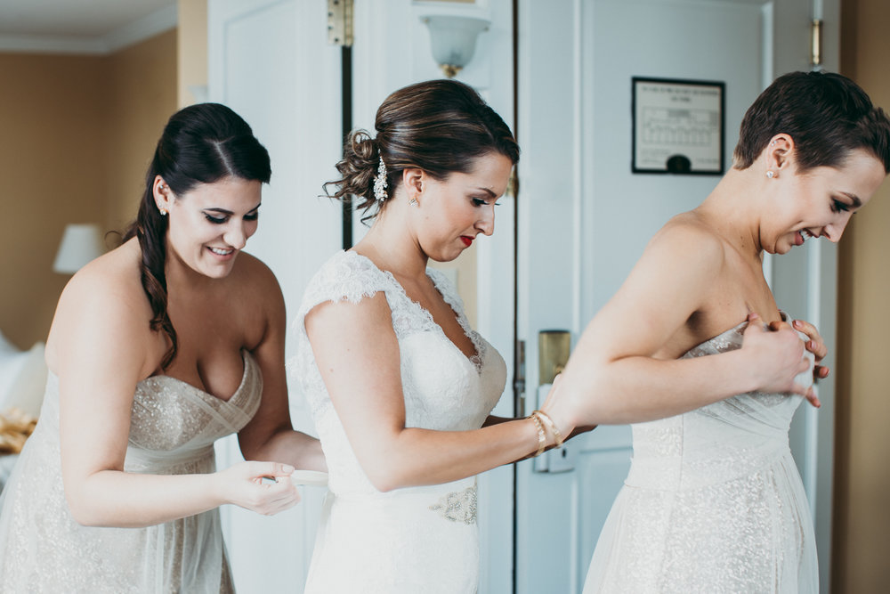 Bride and bridesmaid fixing each other's dresses in a line while smiling.