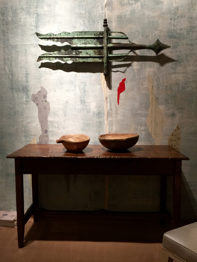 This vignette by Robert Young Antiques incorporates a graphic early banner form weathervane and two antique carved bowls placed atop an unusual banded single plank tavern table.