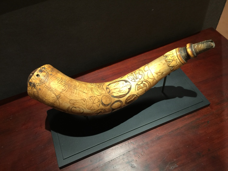 A folk art engraved powder horn featuring unusually relief carved geometric forms, king's head, tree of life and rabbit's head from 1732 was shown by Nathan Liverant and Son, LLC.