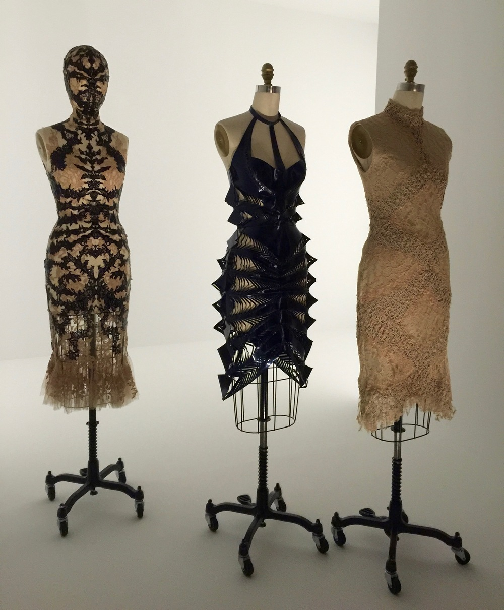 (l) ALEXANDER MCQUEEN, Sarah Burton DRESS, Spring/Summer 2012, pret-a-porter  Machine and hand-sewn nude silk lace bonded with laser-cut black patent leather hand-sewn godets of nude silk tulle, hand-appliquéd with nude silk lace motifs (c) Iris van Herpen DRESS, Spring/Summer 2015, pret-a-porter  Machine-sewn, laser-cut, bonded navy patent leather (r) Iris van Herpen DRESS, Spring/Summer 2016, pret-a-porter  Machine-sewn, bonded nude silk twill and cotton plain weave with overlay of nude cotton lace handwoven with laser-cut nude leather appliqué