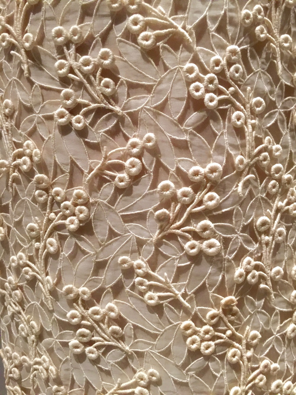 Detail of machine-embroidered cutwork hand-stitched with machine-embroidered guipure lace