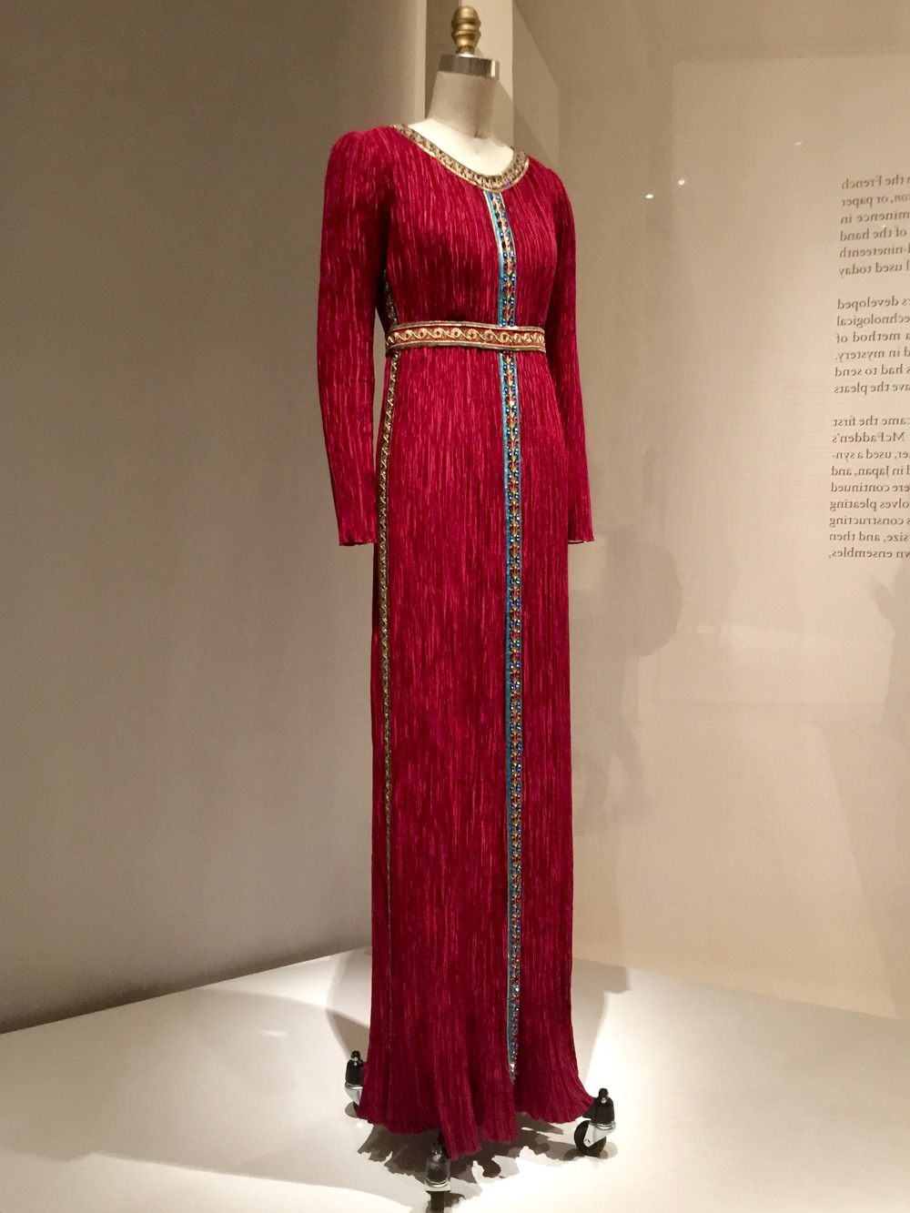 "Mary McFadden DRESS, Ca. 1980, pret-a-porter  Machine-sewn and ""Marii"" machine-pleated red polyester charmeuse, hand-stitched with hand-embroidered trims of sequins, bead, and gold metallic thread"