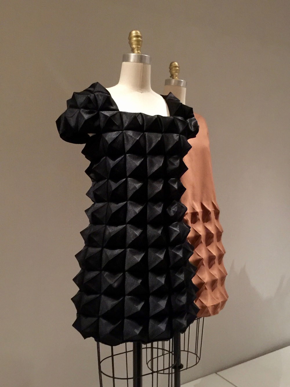 (l) COMME DES GARCONS, Junya Watanabe DRESS, Autumn/Winter 2015-6, pret-a-porter Machine-sewn, heat molded black polyester satin  (r) Pierre Cardin DRESS, 1968, haute couture Machine-sewn, heat-molded brown polyester Cardine (Dynel)