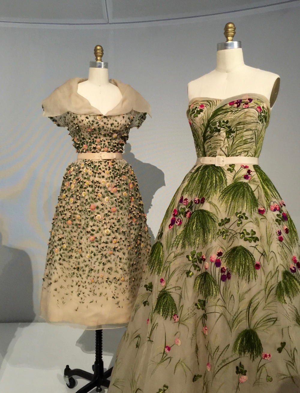 "(l) HOUSE OF DIOR, Christian Dior ""VILMIRON"" DRESS, Spring/Summer 1952, haute couture  Machine-sewn, hand-finished white silk organza, hand-embroidered with artificial flowers in green, pin, yellow, and white silk floss, hand-painted cotton, silk twist  (r) HOUSE OF DIOR, Christian Dior ""MAY"" DRESS, Spring/Summer 1953, haute couture  Machine-sewn, hand-finished white silk organza and net, hand-embroidered with artificial flowers, clover, and grass in green, pink, and purple silk floss"