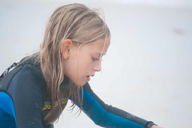 Young surfing girl in wetsuit