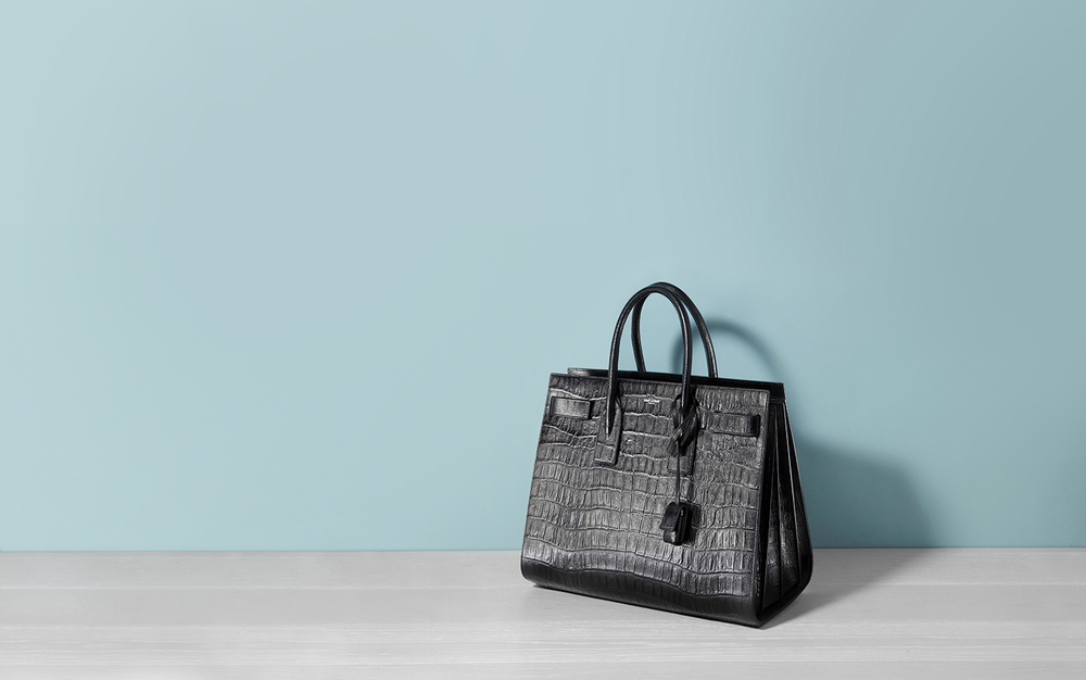 Creative product photography by London still life photographer Chris Howlett. Black animal skin YSL handbag against teal wall.