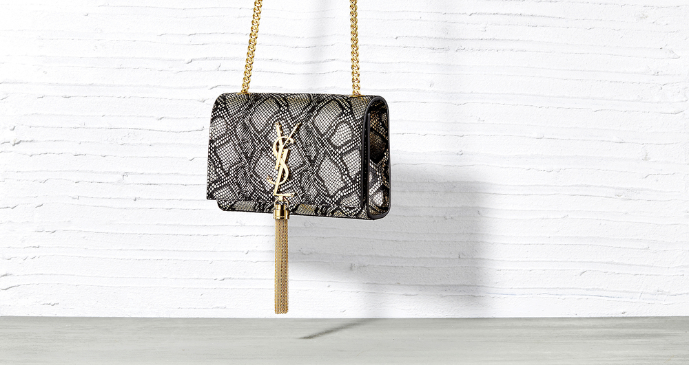 Advertising and product photography by London still life photographer chris howlett. Hanging YSL handbag on white textured background.