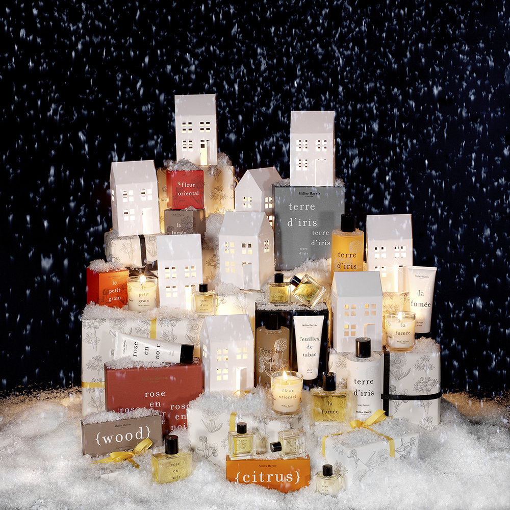 Still Life cosmetics by London advertising photographer Chris Howlett. Perfumes and other cosmetics on presents with model houses snow and candel light