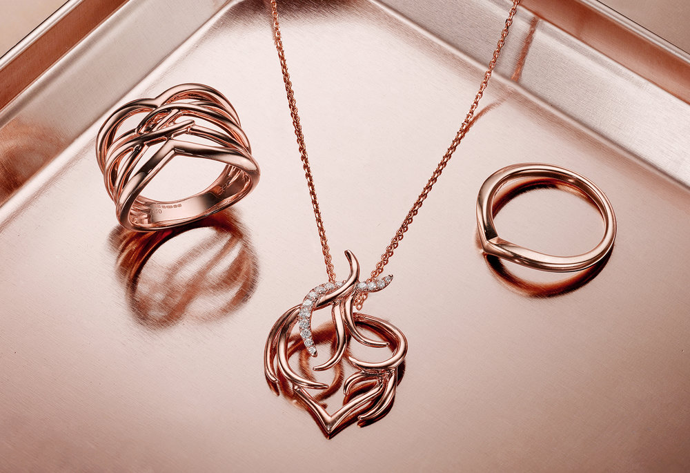 A rose gold diamond encrusted pendant sits on rose gold coloured reflective metal with two rings either side. A fantastic example of creative jewellery photography by London jewellery photographer Christopher Howlett Hatton garden