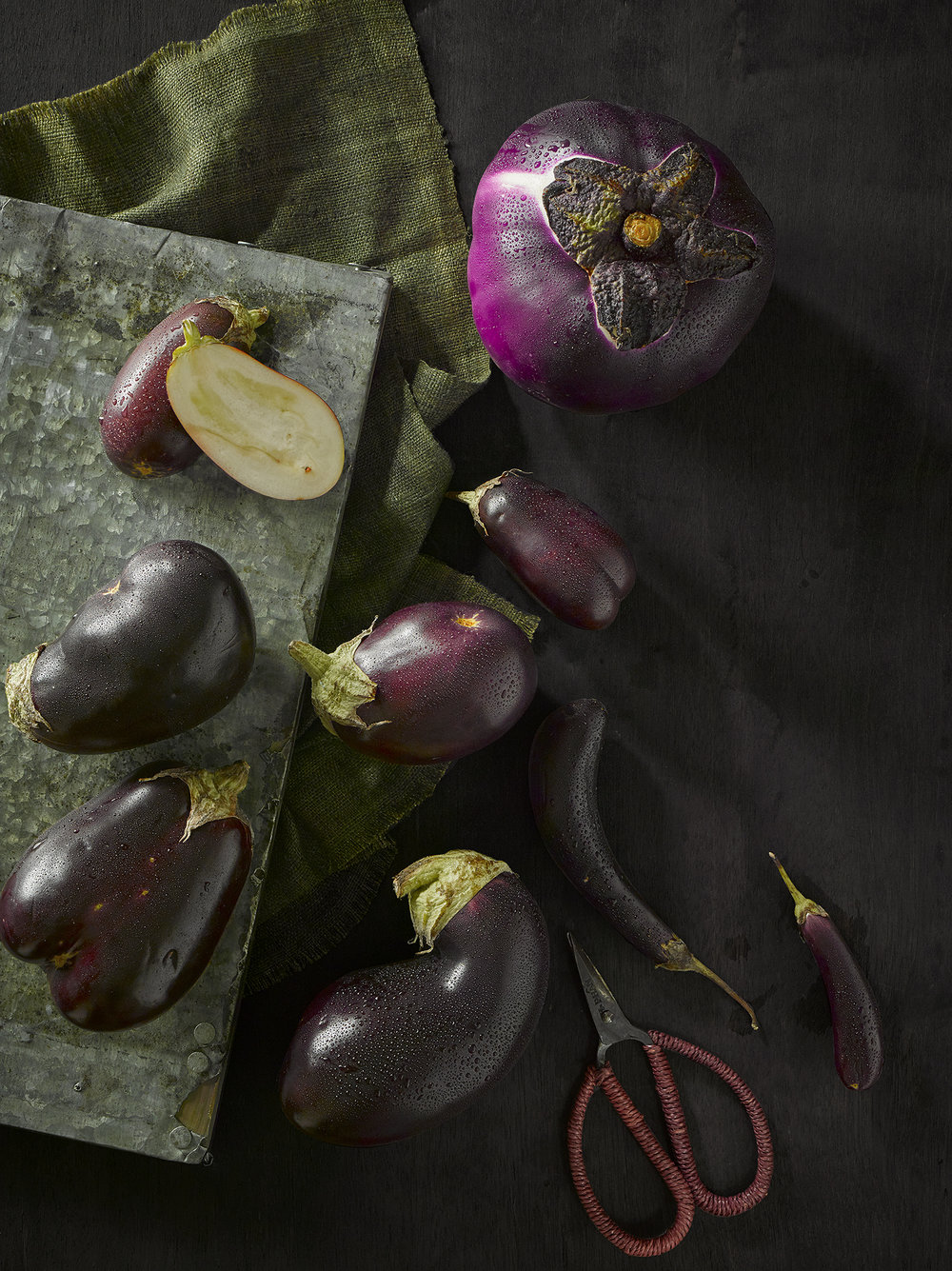 Dark and atmospheric lifestyle food photography. A collection of ugly aubergine ripe and ready to eaten, still life composition of food, fuit and ugly veg by London Food & lifestyle photographer chris howlett
