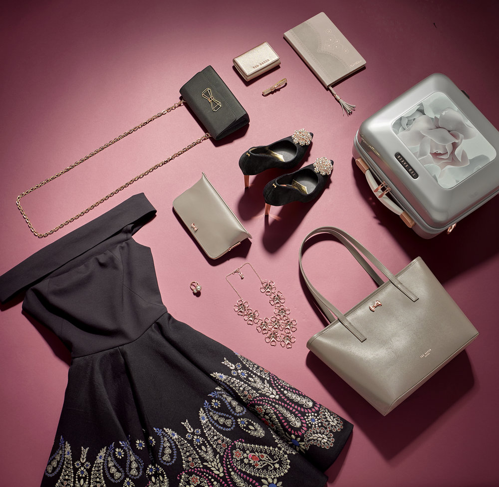 Product photography. Womens accessories, fashion flats on pink. A dress, handbags jewellery shoes and small suitcase make up the creative still life product photography. Shot on location in London studio