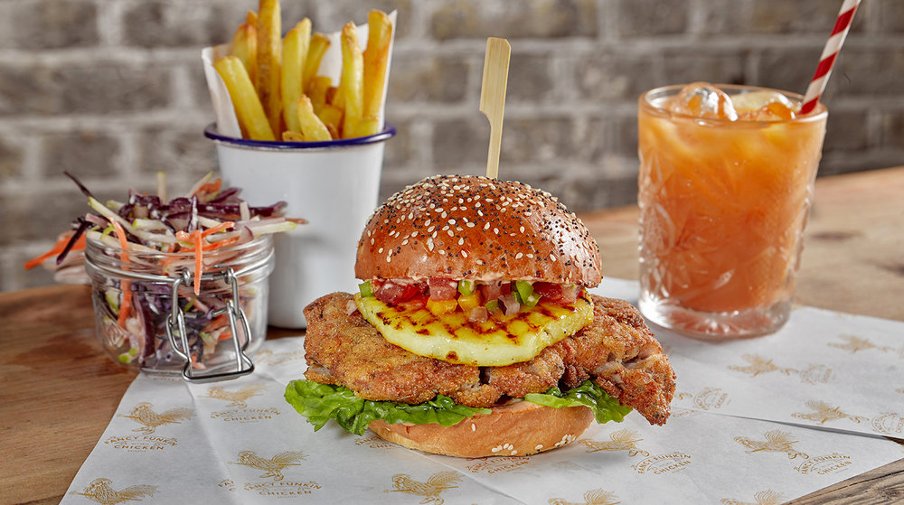 Advertising food photography for chicken restaurant fancy funkin chicken. A tropical burger with cocktail drink chips and coleslaw, south London food packshot photographer