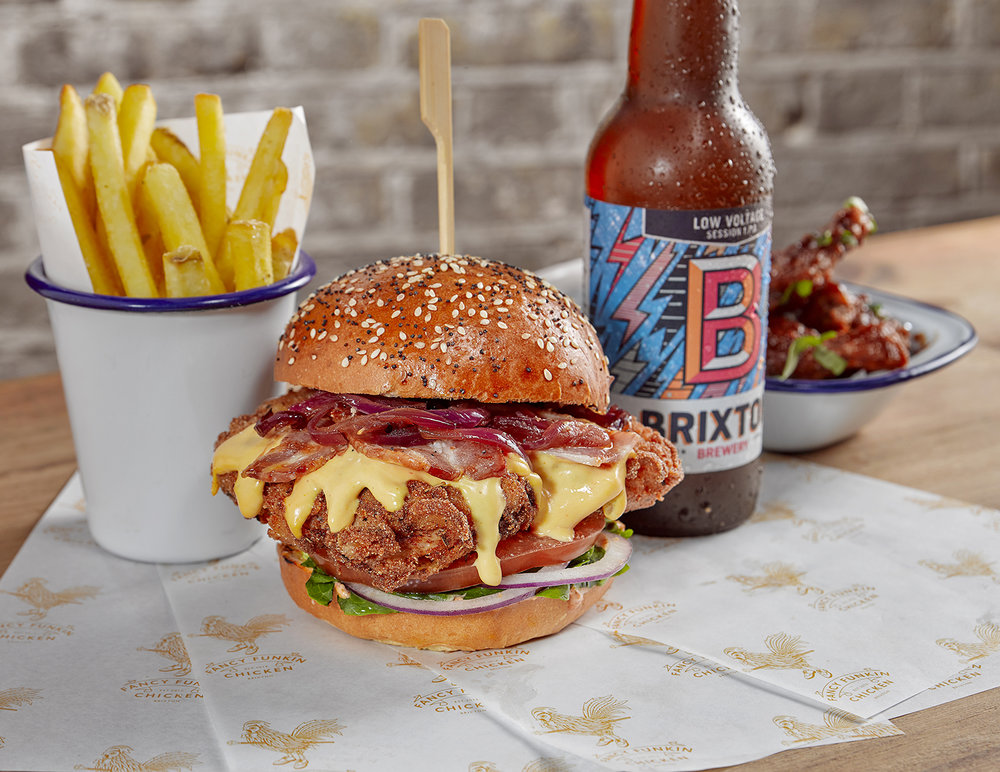 advertising still life food photographer, the chicken cheese melt burger. served with chips and beer
