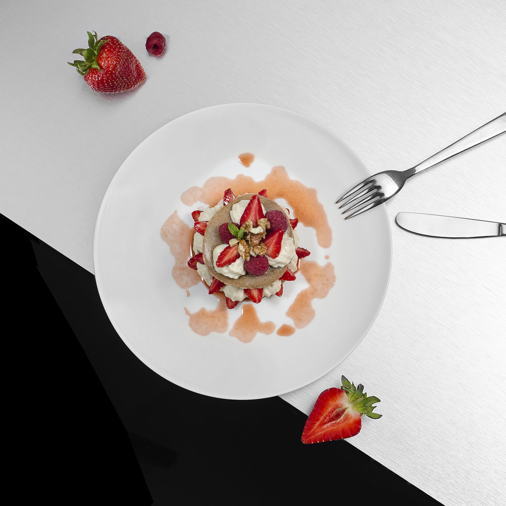 Creative still life food photography. A plate of strawberries with vegan cream photographed in London restaurant by product photographer chris howlett