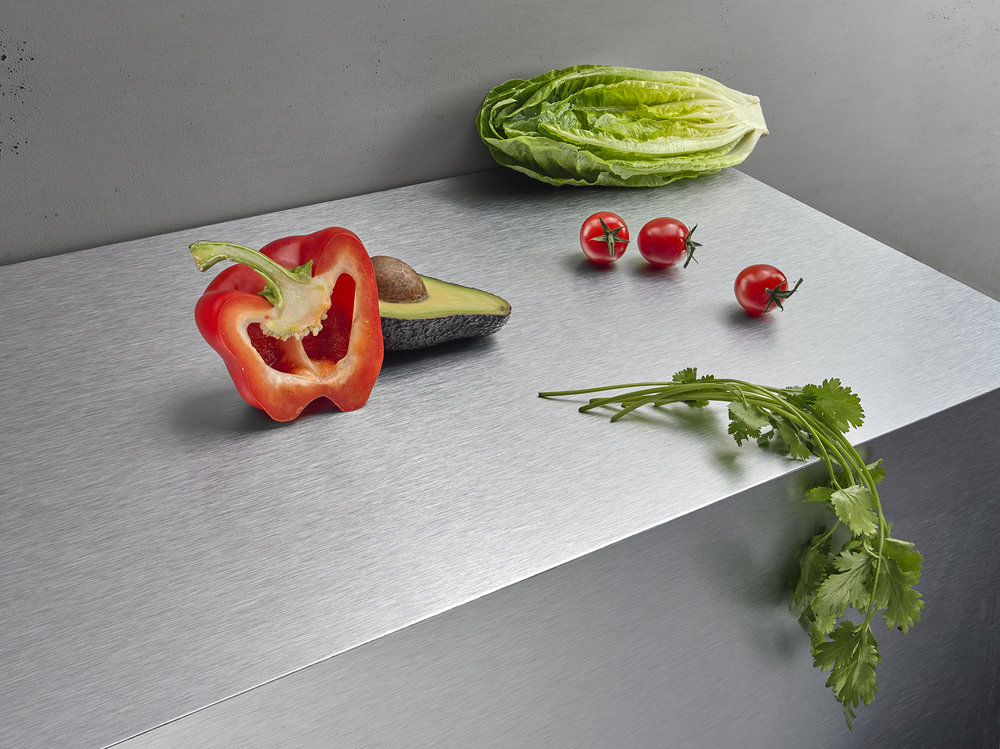 Graphic industrial style product photography with food. Vegetables lay on brushed metal surface. Creative still life London photographer Chris Howlett