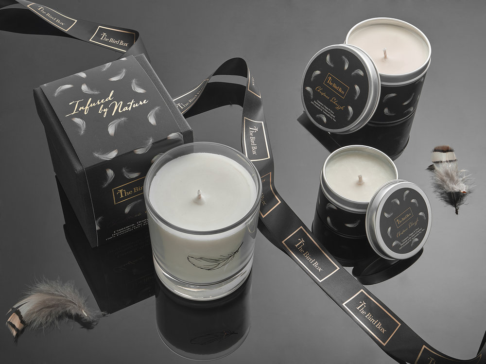 product photography candles on black gloss with gold ribbon and grey feathers. Still life photography from London creative photographer Chris Howlett