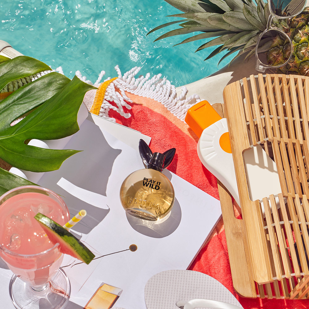 Howlett photography produces creative product photography. A still life poolside theme using perfumes cosmetics and styling props to create a summer vibe around the poolside all shot in london location house