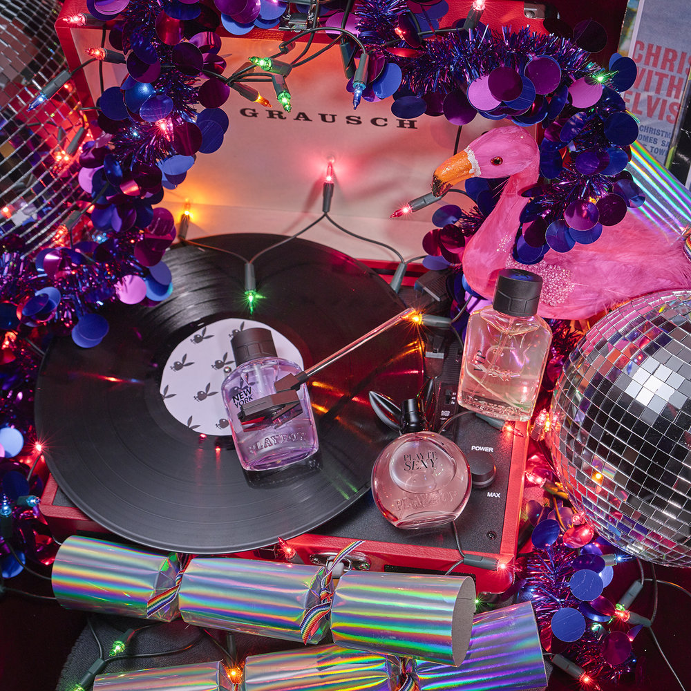 Cosmetic products placed on turntable surrounded by christmas lights disco ball and crackers. packshot by still life photograher chris howlett