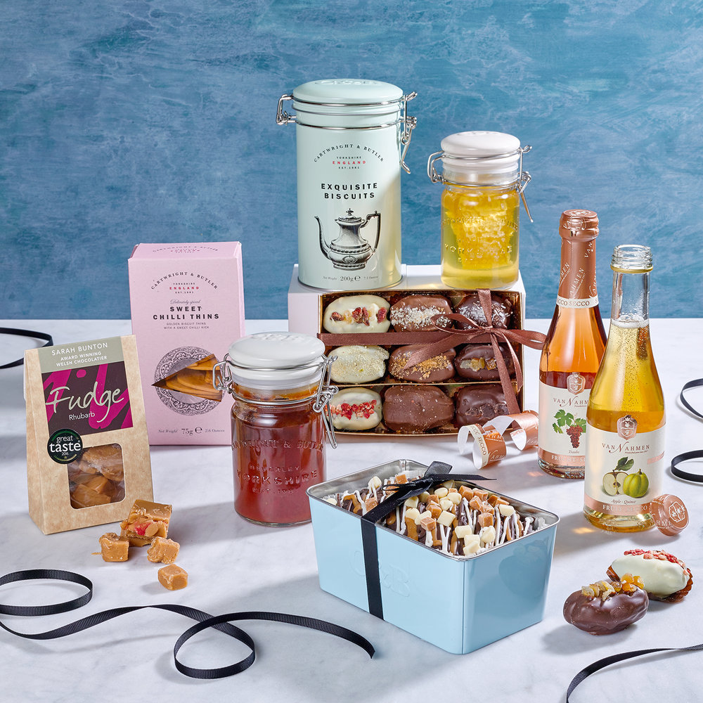 Food still life photography. Hamper collection of sweets including cakes, fudges honey dates and fizzy drinks. Product photographer Chris Howlett