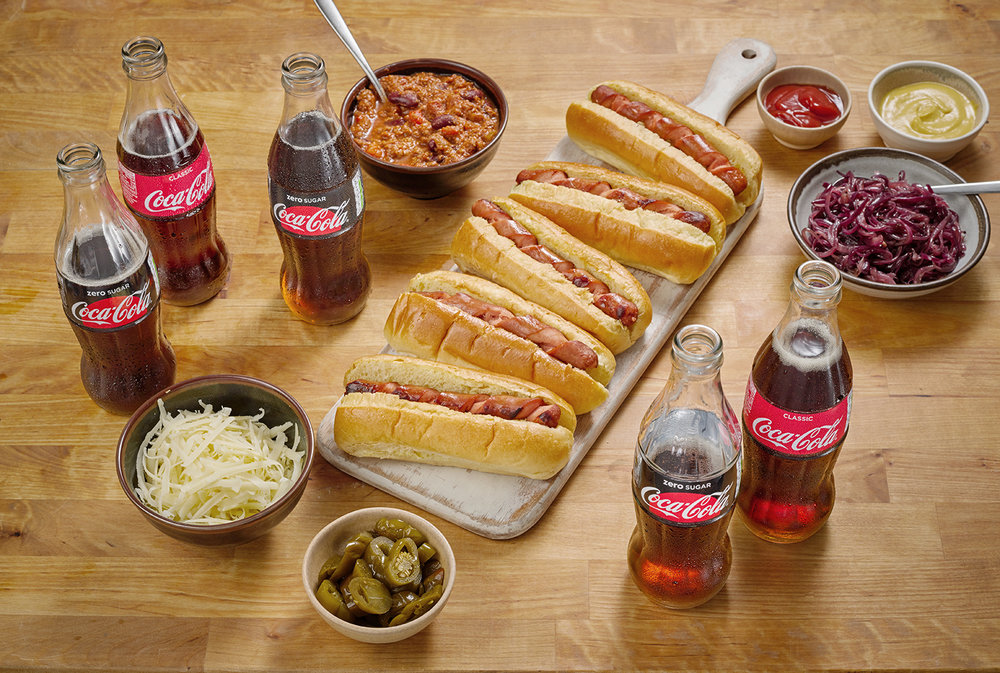 Drink product photography, hog dogs on table surrounded by coca-cola products. Creative still life from london advertising food and drink photographer chris howlett