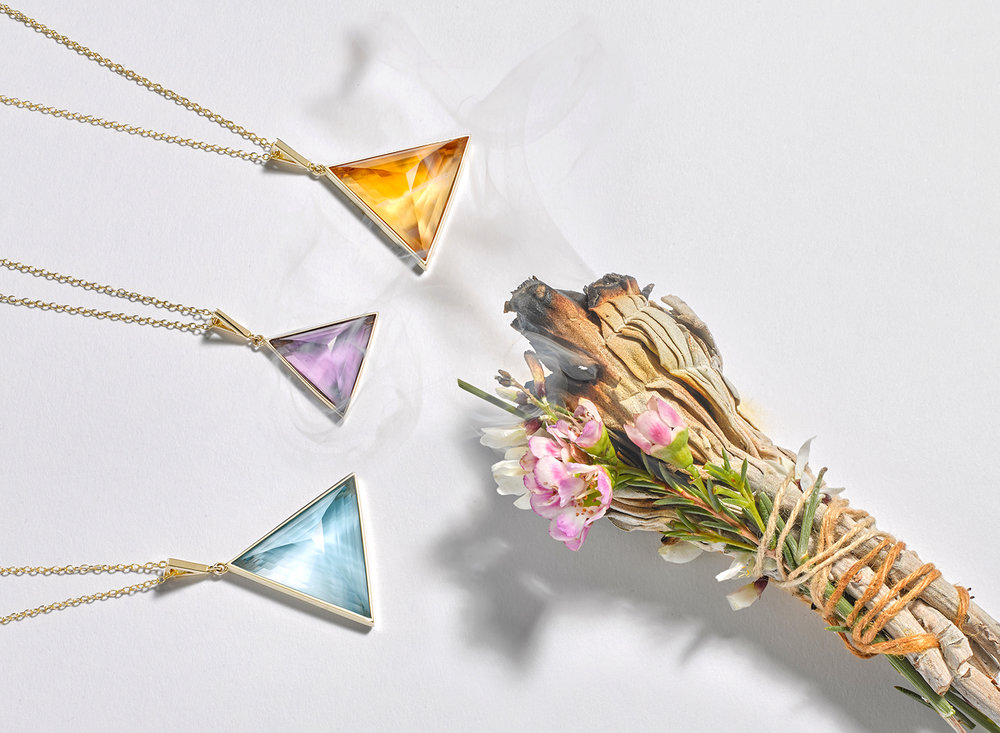 lifestyle creative jewellery photography. A trio of crystal pendants with sage smudge stick and smoke shot in london photographic studio by chris howlett