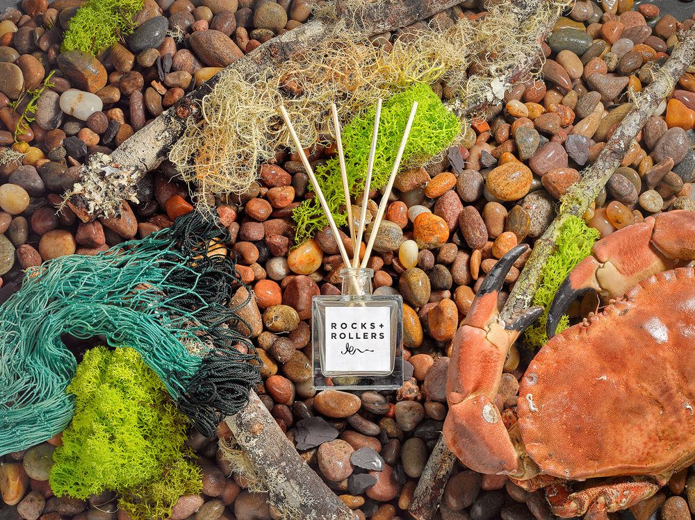 still life product photography from london creative photographer chris howlett. Room fragrance is center image with beach scene, stones sea props an other lifestyle elements