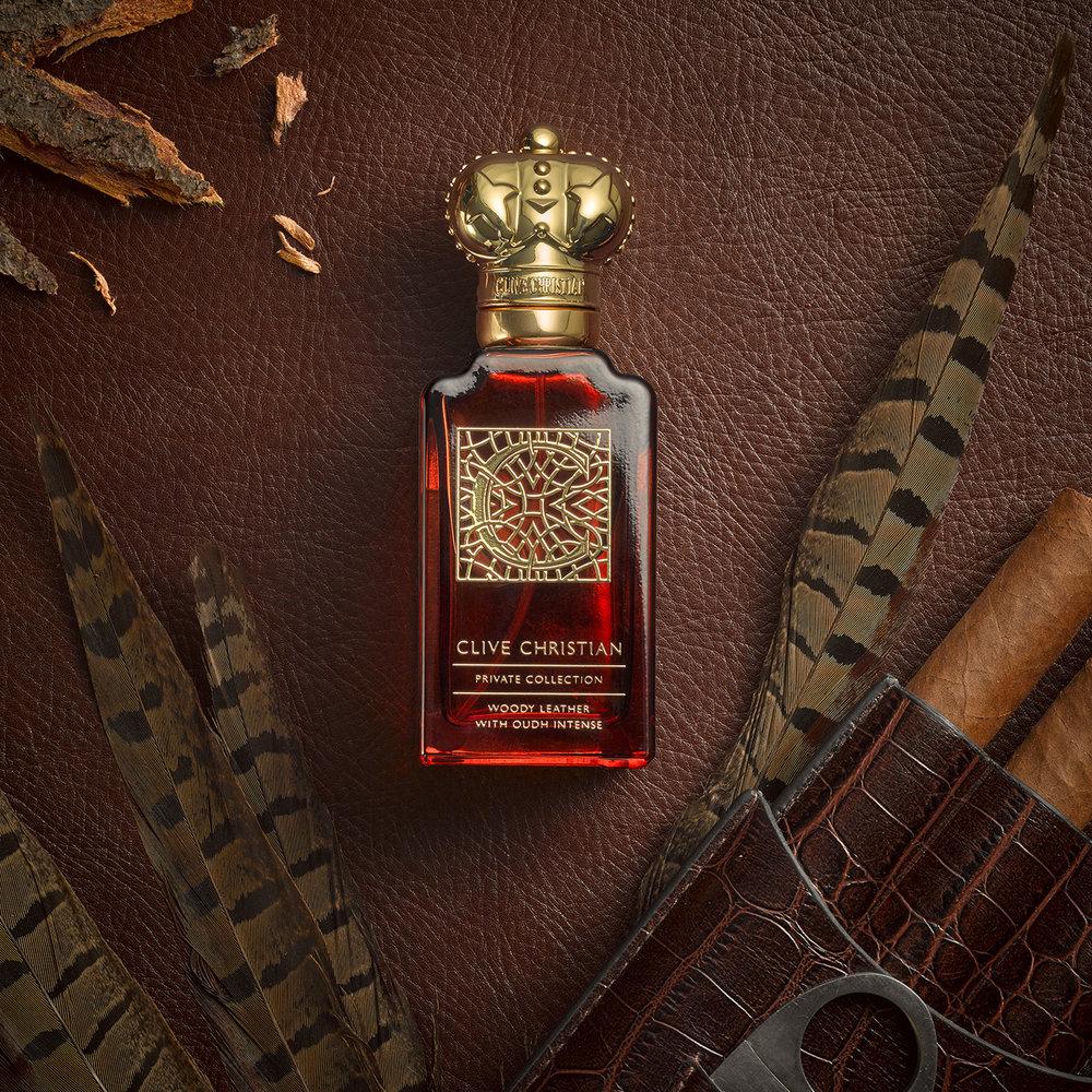still life cosmetics photography. Perfume bottle on mens lifestyle set, feathers leathers and cigars make up this creative product photograph