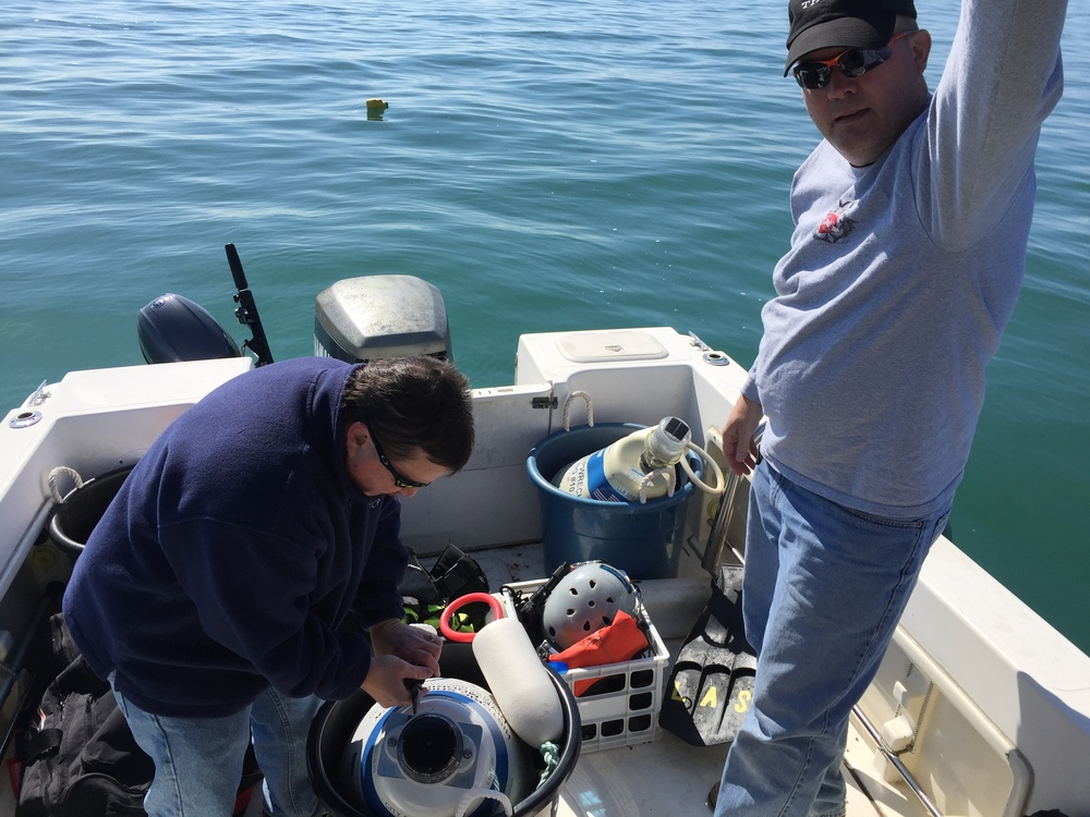 John Toth and Timothy Brown are preparing the mooring balls for deployment.