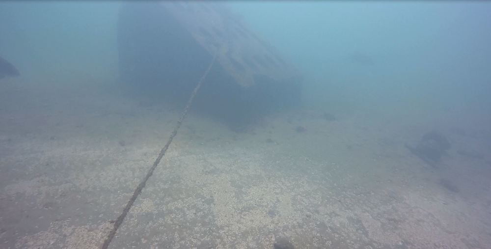 Here is the massive concrete anchor, with the line that goes to the wreck, which makes it easier to find in lower visibility.