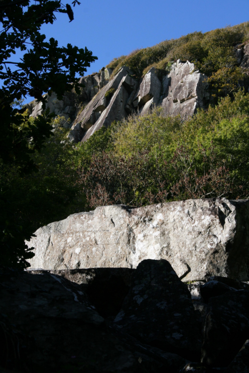 Looking up to the distant crag of slanting slabs with overhangs.
