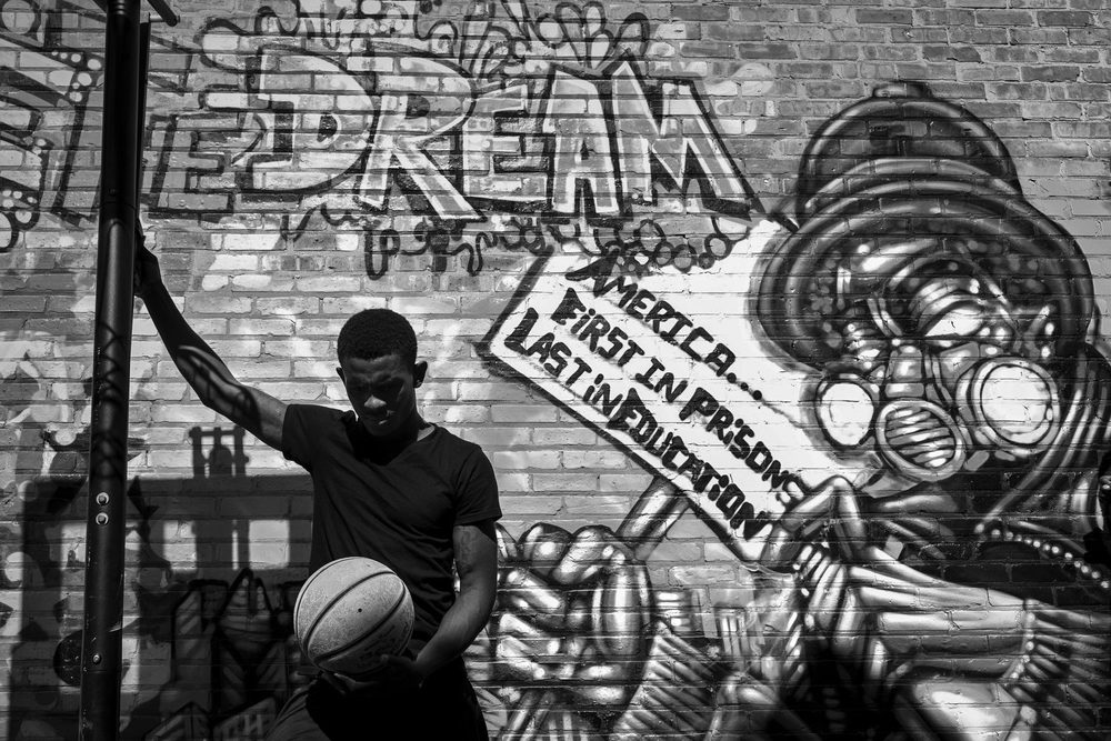 Augustin holds a basketball during orientation for his job at Greencorps Chicago, a job training program through the city for young people with barriers to employment. The orientation took place in the outdoor playground attached to Alternatives, a youth development center in Chicago's Uptown neighborhood.