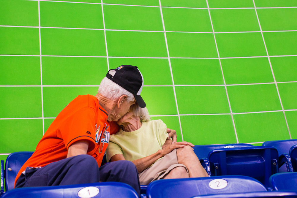 "Lydia and Tony Jimenez kiss for the ""kiss cam"" on the jumbotron at Marlins Park in Miami, FL. They are frequently featured as the last couple and draw ravenous cheers from fans. Last year they attended all 81 games. They met in Puerto Rico and have been married 61 years."