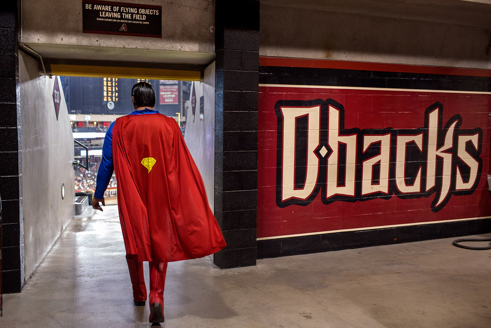 A man dressed as superman walks around Chase Field in Phoenix, AZ, occasionally stopping to give fans high fives and take pictures.