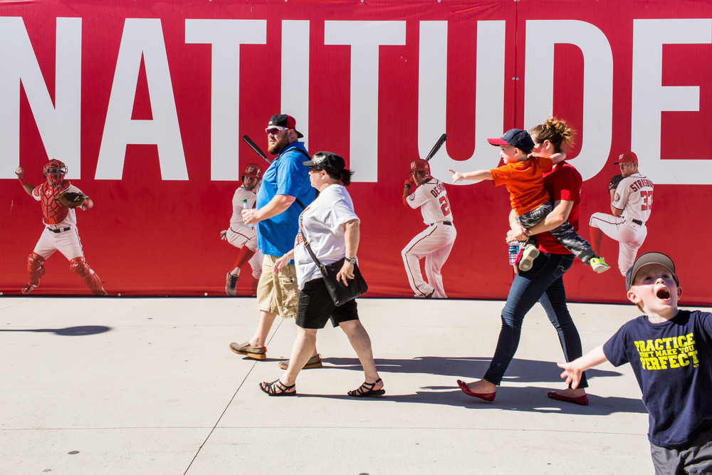 "Washington Nationals fans walk past a banner displaying a portion of the Nationals motto, ""Nothing but Natitude,"" in Washington, D.C."