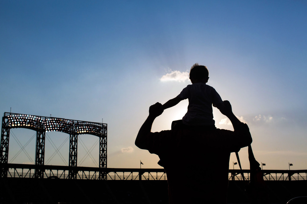 Jay holds his son Luca up on his shoulders at Citi Field in New York, NY.