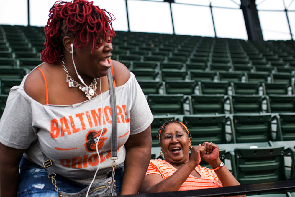 Social worker Joy Aisha Bell, left, laughs with Joann Wilson, who was attending her first baseball game at Camden Yards in Baltimore, MD.