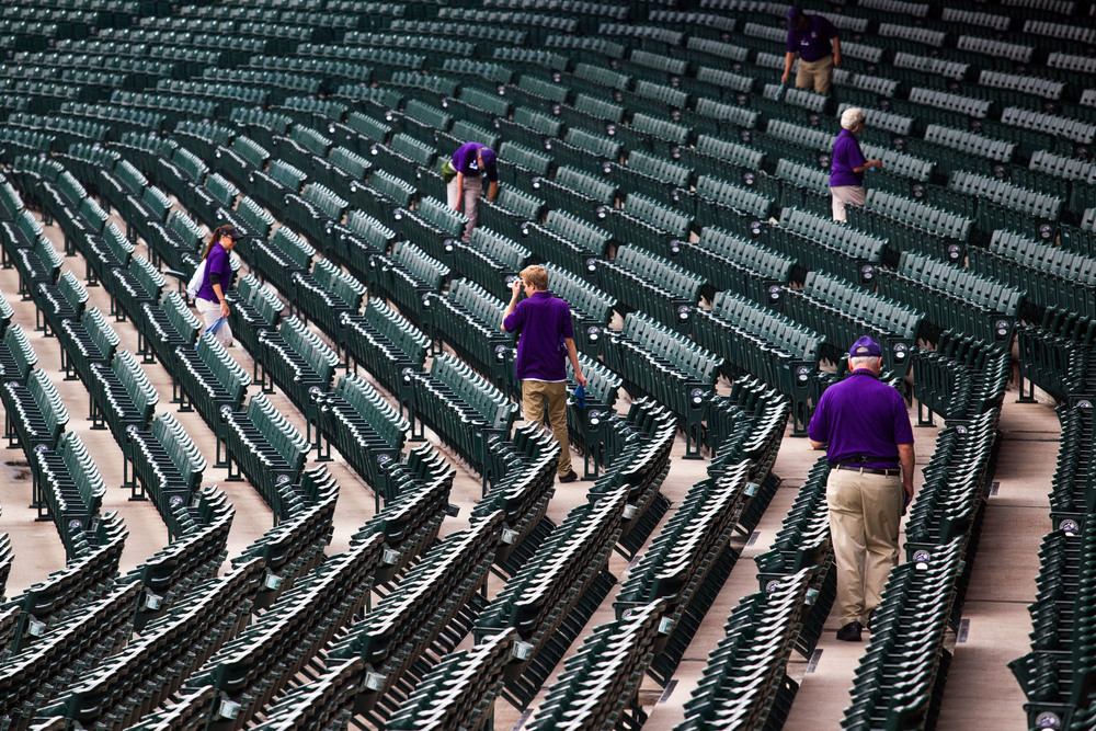 Ushers at Coors Field in Denver, CO walk the seats just after the gates open.