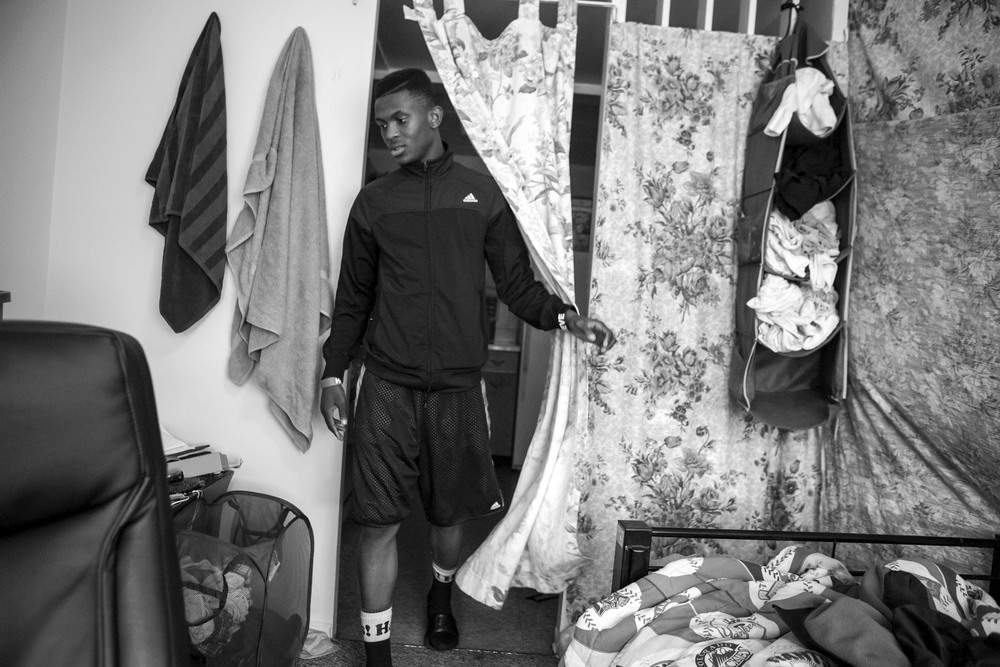 Augustin enters his room in his family's apartment.
