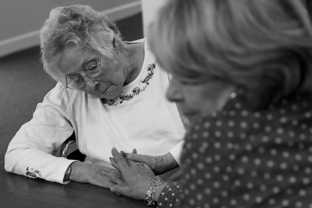 Lucy holds Bonnie's hand at Spring Arbor, a memory care unit in Wilson, NC.