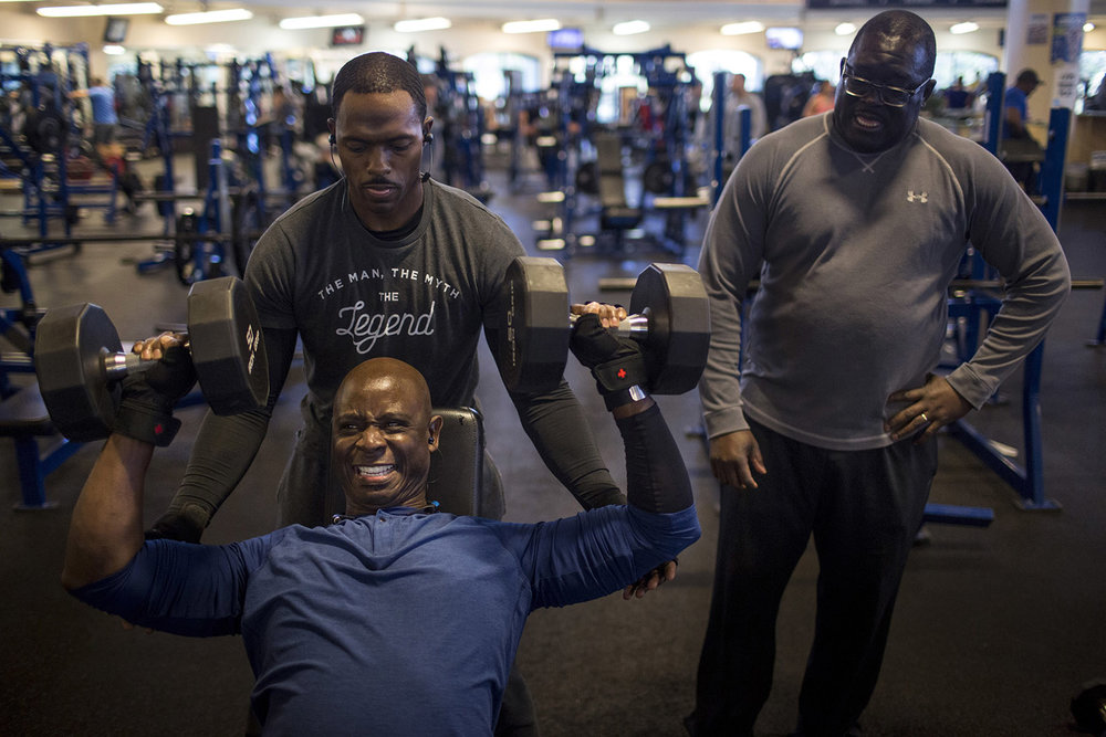 With Elliott Williams looking on, Ritchie King, bottom left, gets a spot from Richard Deane, top left, as he tries to become a member of The 100-Ton Club at the Rambler Fitness Center at Randolph Air Force Base in San Antonio, Texas on February 15, 2017