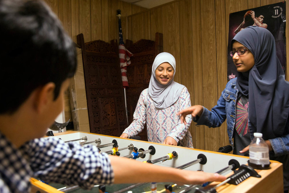 From left, Afnaan Nusayr, Bareera Saif and Raza Qadri play foosball inside a large trailer, which serves as a temporary mosque, next to the site of the Victoria Islamic Center in Victoria, Texas on May 26, 2017.