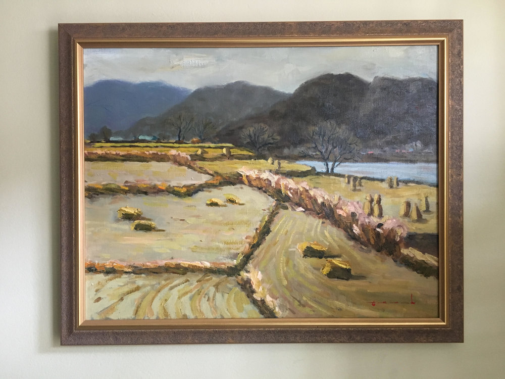 "Autumn 가을 - Oil on canvas16"" x 20"", framedStarting bid:  $200This landscape depicts the late afternoon on harvest day. The tall cylindrical objects on the right side are볏짚  ""byeot-jip"" (hay bales).  The inclusion of the lake speaks to a favorite pastime of many Korean farmers: fishing as a means to relax after a long day of harvesting."