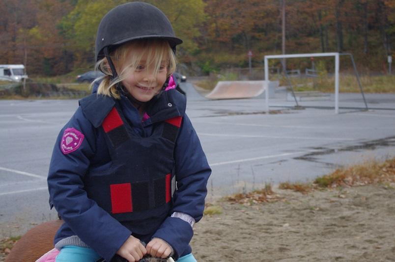 Blide 2.klassinger med hjelm og sikkerhetsvest koste seg med ponniridning.