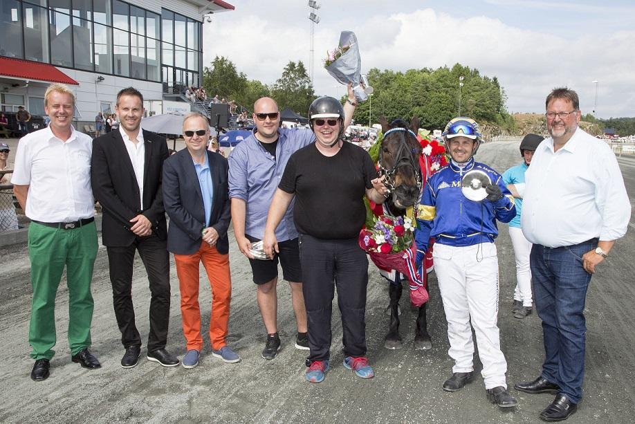 Tor Ørjan Johansen, i svart t-skjorte ved Åsrud Viljas hode, klatret opp på 6.plass på trenerstatistikken på Sørlandets Travpark etter NM-seieren. Foto: Hesteguiden.com.