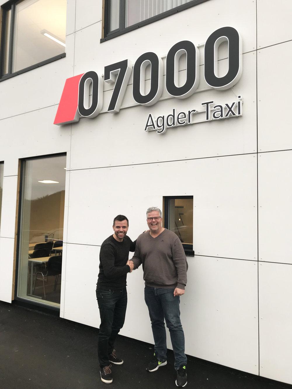 Carl Fredrik Holst hos 07000 Agder Taxi og Ingvar Ludvigsen feirer at en samarbeidsavtale er på plass. Foto: 07000 Agder Taxi.